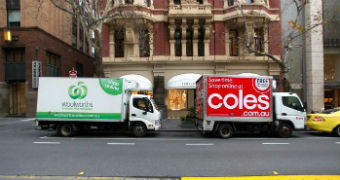 Coles and Woolworths delivery trucks parked side by side on the street.