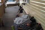 A man sleeping rough on a verandah