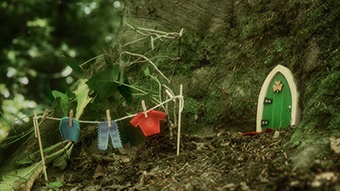 A tiny green door sits at the bottom of a massive tree with a miniature washing line strung up out the front.