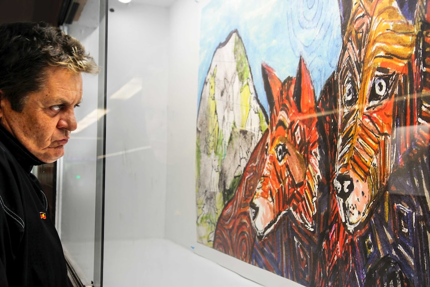 Peter Waples-Crowe looks at one of his mixed media pieces in his Dirty Dingo series.