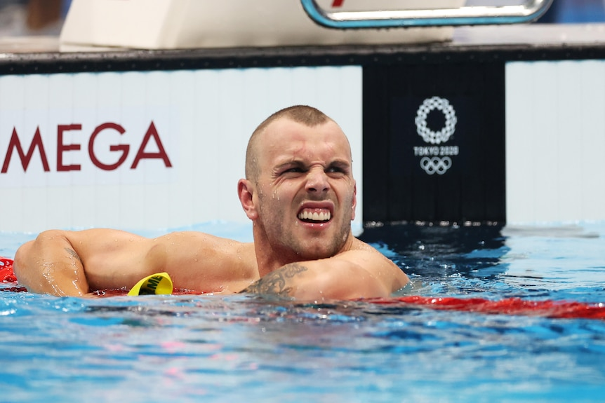 An Australian male swimmer leans over the ropes after his heat at the Tokyo Olympics.