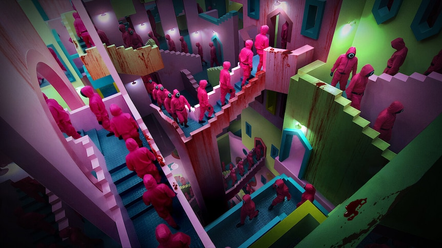 People in pink jumpsuits walk through a colourful labyrinth of staircases