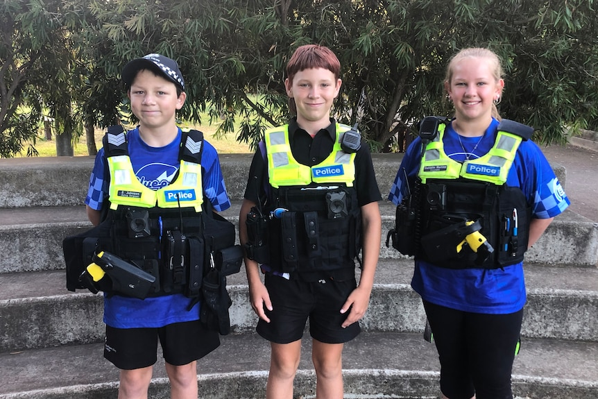 Three young school students dressed up in police gear.