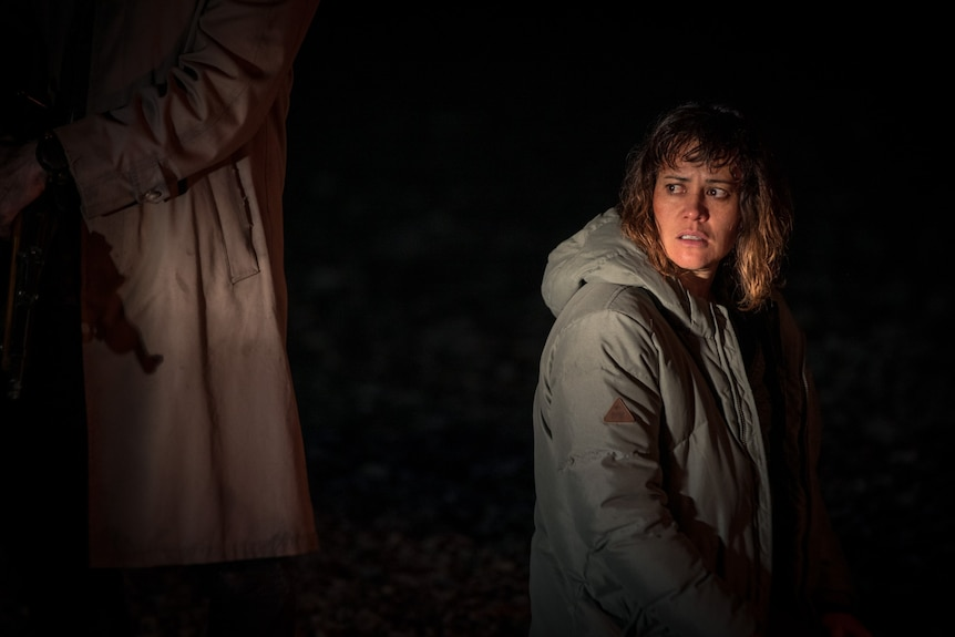 A Maori woman in her 40s looks afraid. She is standing in the dark, looking behind her at an unseen threat.