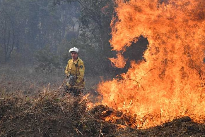 A firefighter standing in front of burning bushland