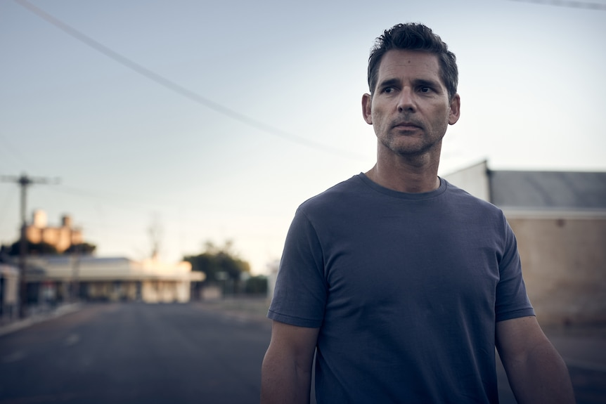 50-year-old white man with short salt-and-pepper hair wearing a blue tee shirt, with twilight country town streetscape behind.