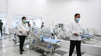 Indonesian president Joko Widodo in a face mask an white coat walks past hospital beds