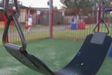 A swing in a park with children in the background
