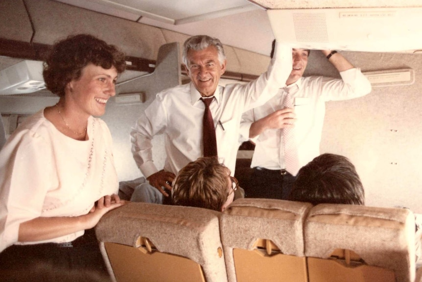 Ewart and Hawke standing in aisle of a plane.