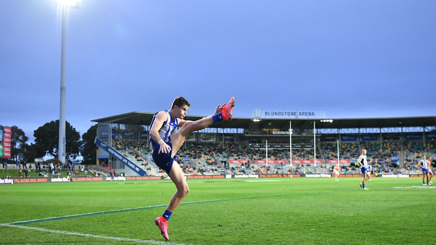 North Melbourne's Bailey Scott completes a shot for goal at Bellerive Oval against the GWS Giants.