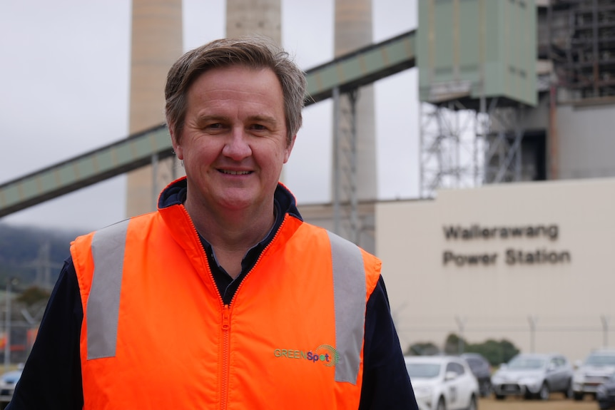 A man in a high-visibility vest stands in front of a defunct coal-fired power stations.