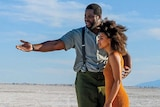 A tall Black man gestures to a short Black woman as they stand in a desert
