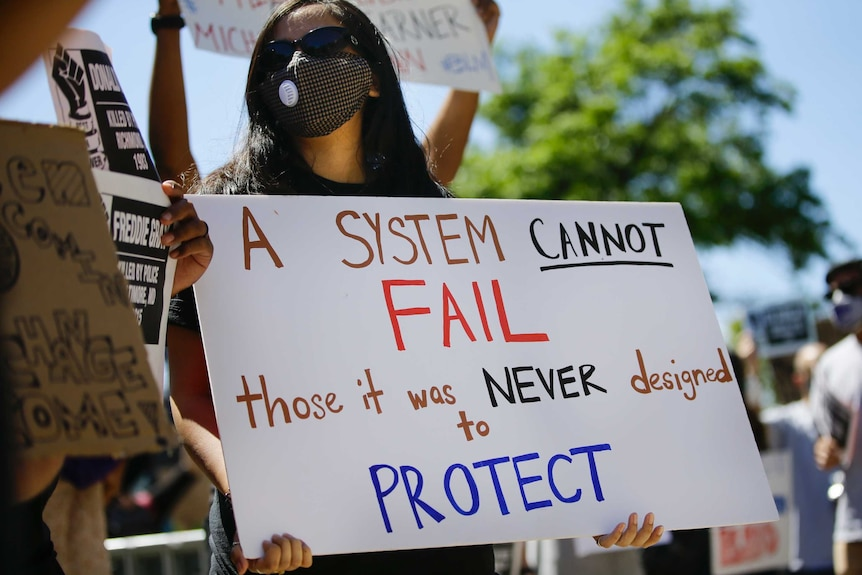 A young female in a black face mask and holding a white sign stands in a rally under blue skies.