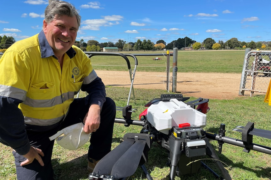 A smiling man leaning next to a drone.