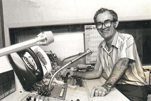 Black and white photo, Milton Moorhead sitting at a radio panel, microphones in shot, smiling.