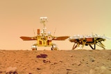 Chinese Mars rover Zhurong sits on the dusty ground near its landing platform bearing a Chinese flag.