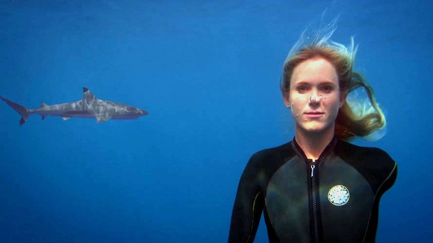 A woman with one arm wears a wet suit underwater as a shark swims in the background.