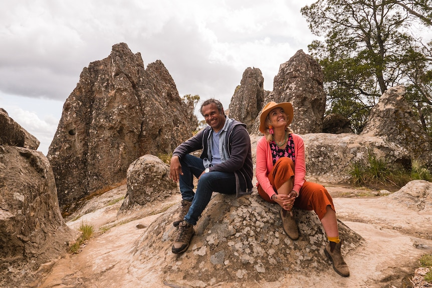 An Aboriginal man in his late 40s and a white woman in her early 40s sitting on a rock on a beach