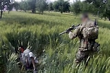 SAS soldier points gun at Afghan man