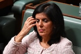Julia Banks pushes her hair off her face