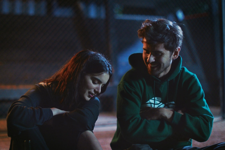 A 20-something woman and man in hoodies sitting close to each other outside at night, smiling.