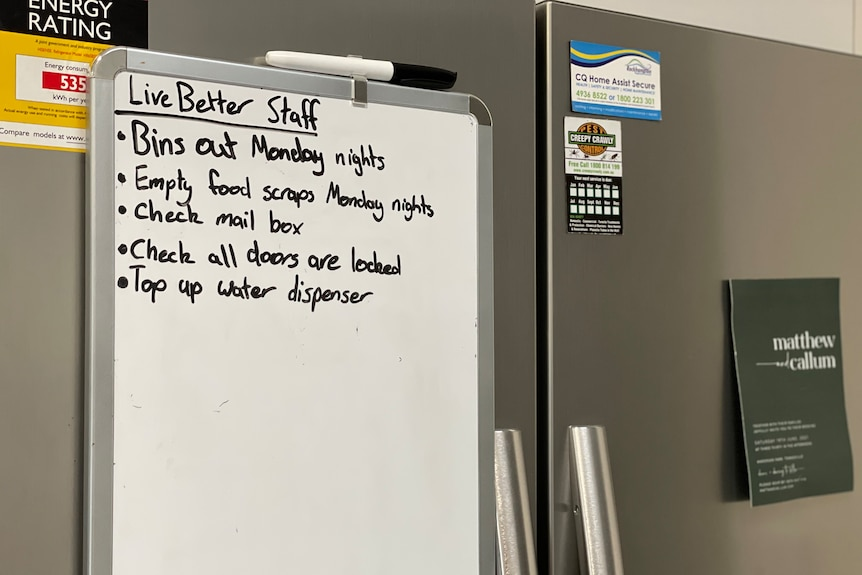 A whiteboard on a fridge with tasks listed, including bins and emptying food scraps.
