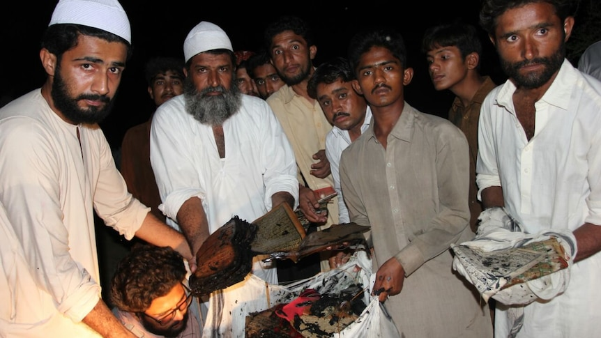 Leaders of Bharchundi shrine show burnt copies of the Koran.