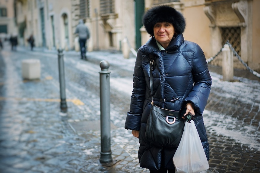 A woman stands smiling in an Italian street.