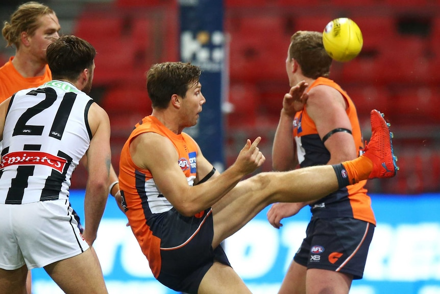 An AFL player hooks the ball towards goal with his right foot, as other players look on.