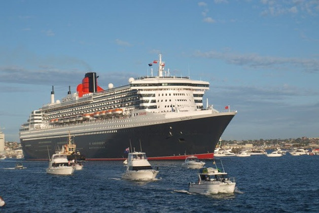 A long shot of the Queen Mary II sailing into harbour with small vessels in front of it.