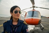 A woman in aviators and pilot outfit stands in front of a red chopper
