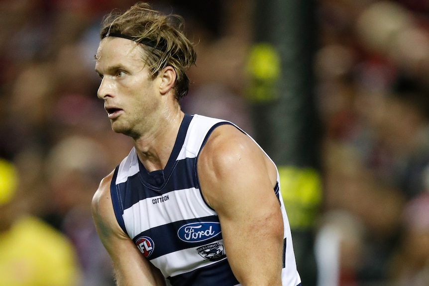 A Geelong AFL player holds the ball in two hands as he prepares to kick to a teammate.