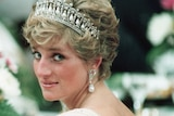 Princess Diana in a low-backed pearl gown and tiara looking over her shoulder