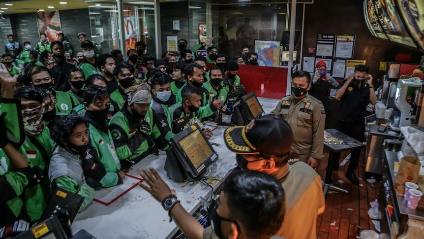 Dozens of food delivery riders queue up at a McDonald's outlet in Bogor, Indonesia.