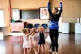 A young woman teaching four little girls dressed in ballet costumes how to twirl.