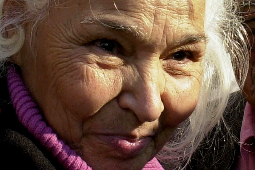 A woman with white hair smiling, while looking away from the camera.