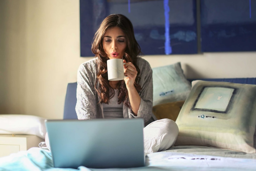 A woman sits in bed working on a laptop