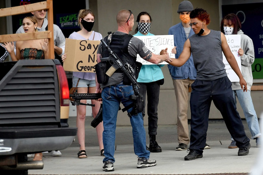 A heavily armed man shakes hands with a protester