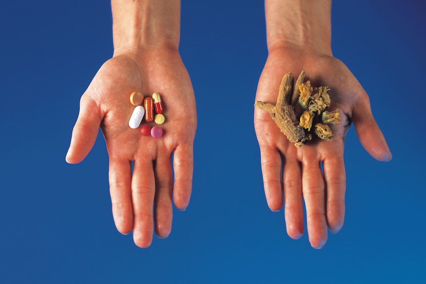 Hands holding pills and herbs separately (Thinkstock: Comstock)