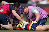 An Adelaide Crows AFLW player lies on the ground and is attended to by medical staff after being concussed.