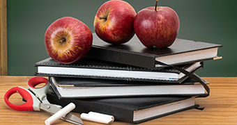 Apples and scissors on some notebooks on a desk.