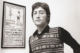 John Lennon stands next to the poster than inspired Being for the Benefit of Mr Kite.