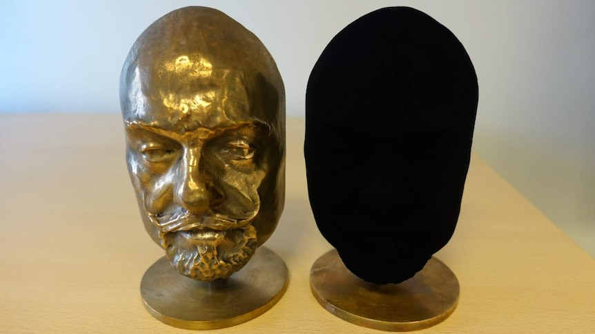One ordinary bronze cast and another that has been coated with Vantablack that is completely black