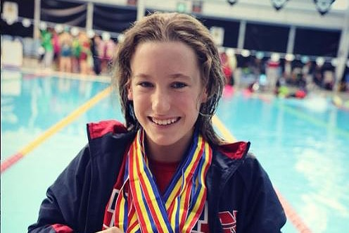 A girl in a wheelchair with medals around her neck next to a competition pool