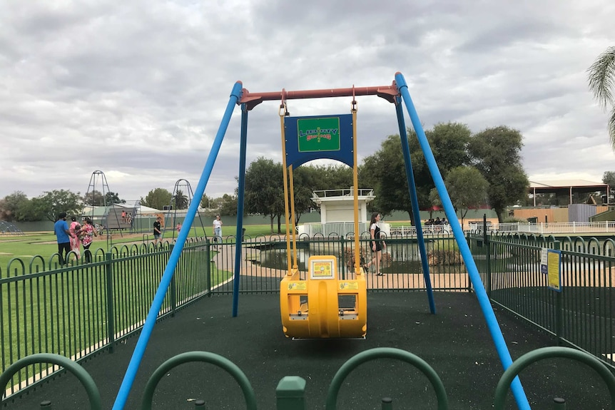 A Liberty swing in an isolated fenced-in enclosure at a playground.