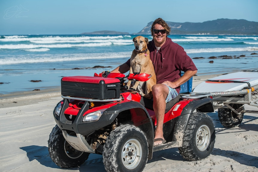 Luc Longley on a quad bike on the sand at a beach with his dog on the seat in front of luc