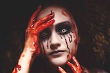 A woman in scary Halloween make-up, including blood smeared on her hands and running down her eyes and white contact lenses