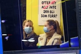 two women in masks look at each other as they chat on a train