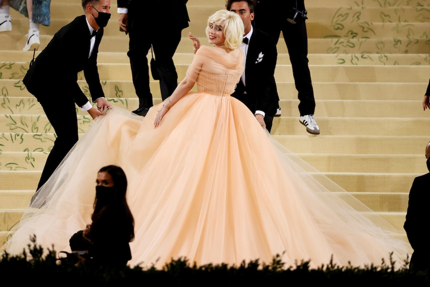 Billie Eilish looks back over her shoulder while wearing a peach tulle ball gown.