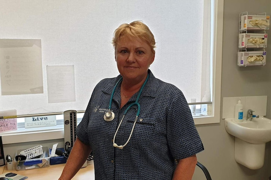 Woman in blue shirt with stethoscope around her neck